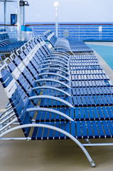 Row of folding lounge chairs on deck
