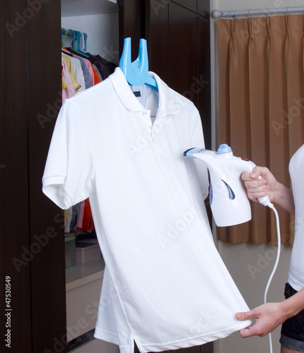 A woman ironing t-shirt with a small steam ironing machine