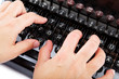 Female hands typing on the keyboard of the old mechanical typewr