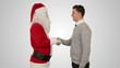 Santa Claus and Young Businessman against white, shaking hands