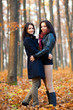 Two young girlfiriends hugging in the woods