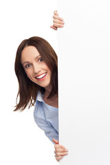 Woman peeping over blank poster