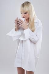 junge blonde Frau im Männerhemd  trinkt Tee aus einer Tasse