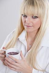 junge blonde Frau mit Tasse Tee in der Hand