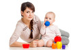 baby girl and mother playing together with cup toys