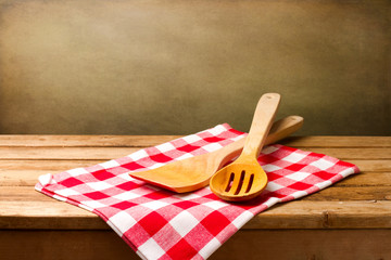 Kitchen utensils on tablecloth on wooden table