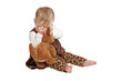 Cute baby in brown velvet dress plays peek-a-boo with stuffed an
