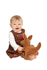 Happy baby in brown velvet dress sits with stuffed toy animal