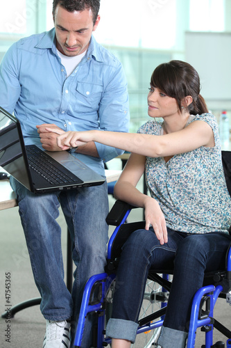 woman in wheelchair being shown something on a laptop