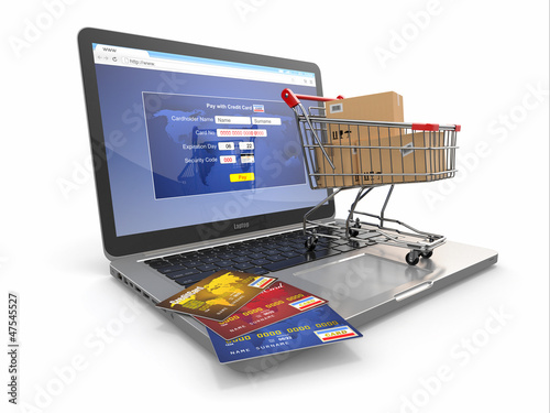 E-commerce. Shopping cart and credit cards on laptop