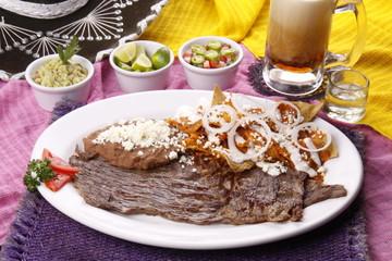 Chilaquiles en salsa roja con bistec. Comida mexicana