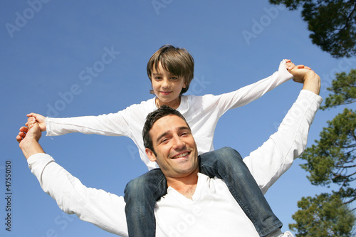 Little boy riding on his father's shoulders