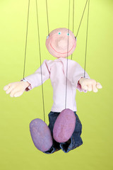Wooden puppet on green background
