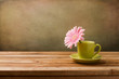 Pink daisy flower in green cup on wooden table