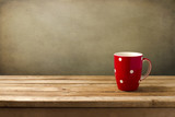 Red cup with dots on wooden table over grunge background