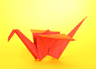 Origami crane on yellow background.