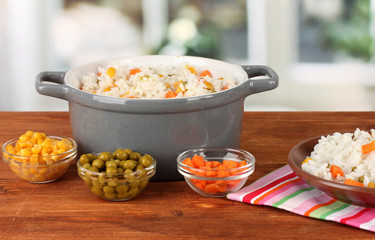 Risotto in  gray pot on wooden table on bright background
