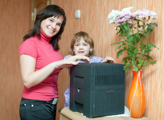 Woman and child uses humidifier