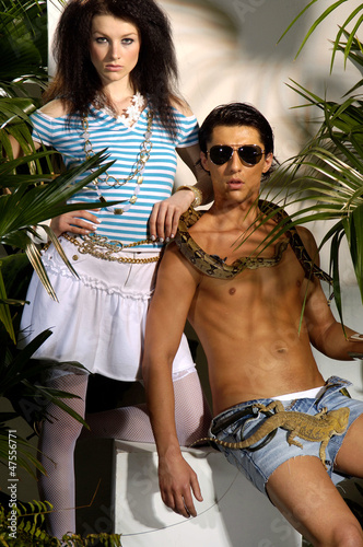 couple young male model with snake in tropical green forest