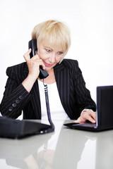 Attraktive Frau im Büro am Telefon