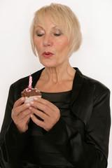 Frau pustet Kerze auf Muffin aus