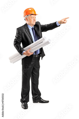 Mature architect holding a blueprint and pointing