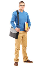Smiling male student with bag holding notebooks