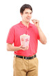 Young smiling man eating popcorn