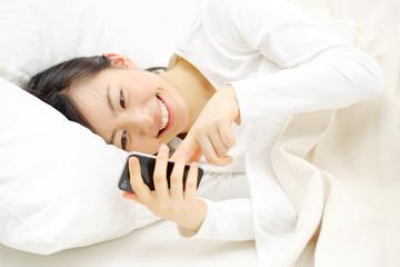 スマートフォンを寝ながら使う女の子