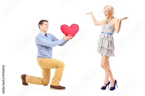 Boyfriend on knee giving a heart to his excited blond girlfriend