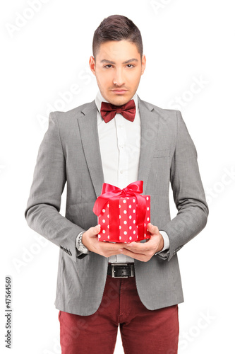 A handsome guy   with bow tie holding a gift