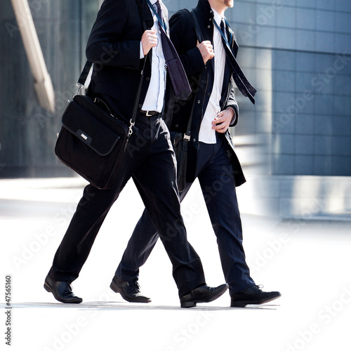 Two businessmen walking on the background of the office.
