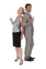 Couple stood back to back holding champagne glasses