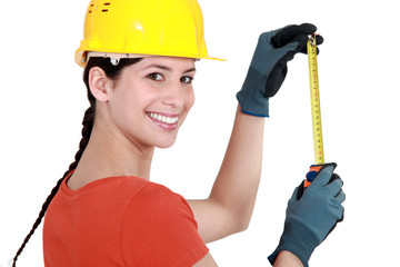 Young female laborer using measuring tape