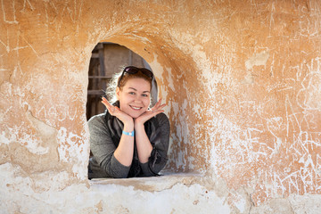 Caucasian woman in ancient wall loophole cheerful and happy
