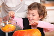 Little girl hollowing out a pumpkin