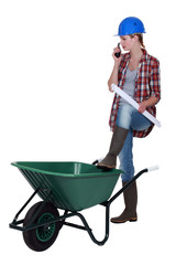 Female construction worker stood with wheelbarrow