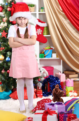 Upset by little girl near the Christmas tree in festively