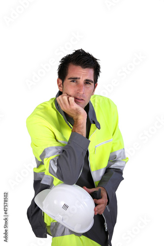 Studio portrait of a man in fluorescent work clothes and helmet