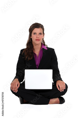 A businesswoman seated on the floor.