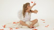 Little girl dressed as Cupid surrounded with paper hearts