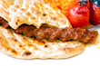 Traditional Adana Kebab served with pita bread
