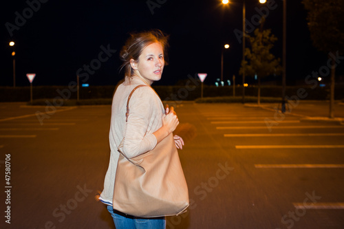 Scared woman running from her pursuer in a deserted parking