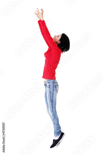 Teen girl jumping in air trying to catch something.