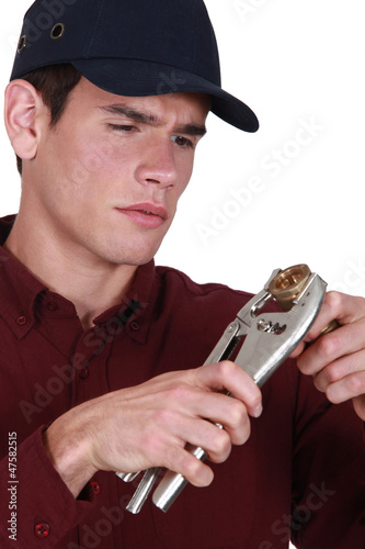 Plumber holding wrench and pipe
