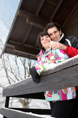Couple stood by snow covered chalet