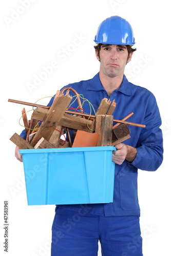 Construction worker recycling old wood