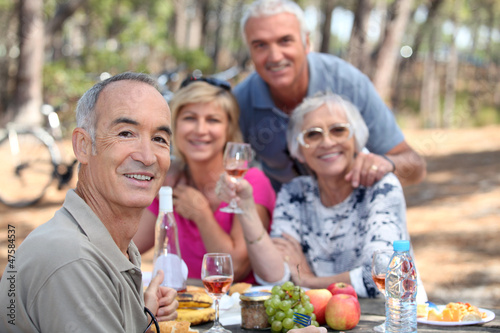 Older people eating in a field