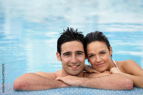 Couple stood together in swimming pool