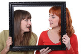Two women poking heads though empty picture frame